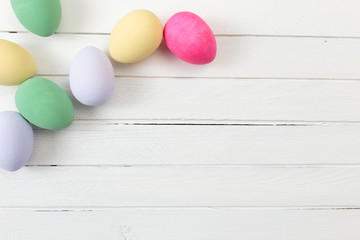 Easter eggs painted in pastel colors on white wooden background