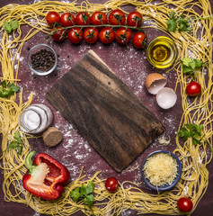 raw pasta, lined frame around ingredients border ,place for text on wooden rustic background top view