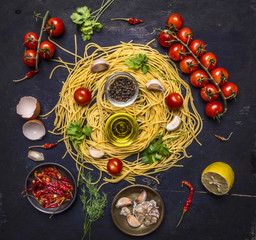 Ingredients for cooking pasta with tomato on a branch, oil, garlic and pepper, egg on wooden rustic background top view close up