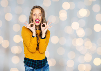 happy young woman or teen showing ok hand sign