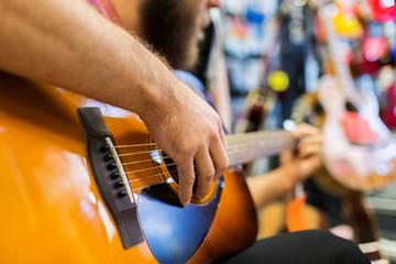 Spoed Foto op Canvas Muziekwinkel close up of man playing guitar at music store