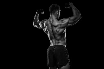 Rear view of healthy muscular young man with his arms stretched