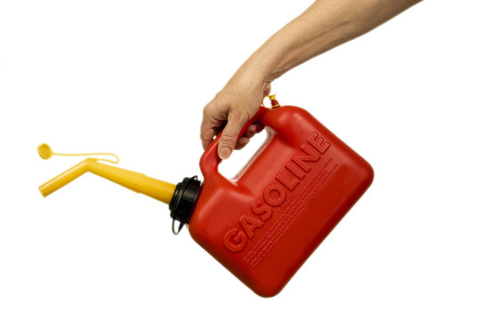 Horizontal shot of a hand holding a red gasoline or petrol container.  Isolated on white