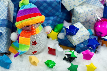 Snowman and gift box with small star paper on the snow field.