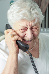 elderly woman speaks on the phone