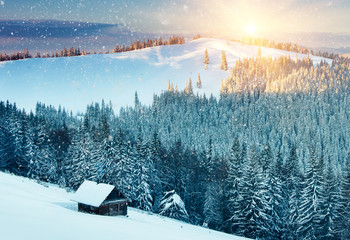 Colorful sunset in the winter mountains. Snowy forest and hunting lodge on the background of falling snowflakes.
