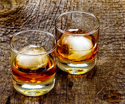 Two cocktail glasses with an amber alcoholic beverage, Rusty Nail,  and round ice cubes on a rustic barn wood background.