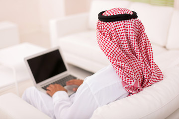 rear view of muslim man sitting on sofa