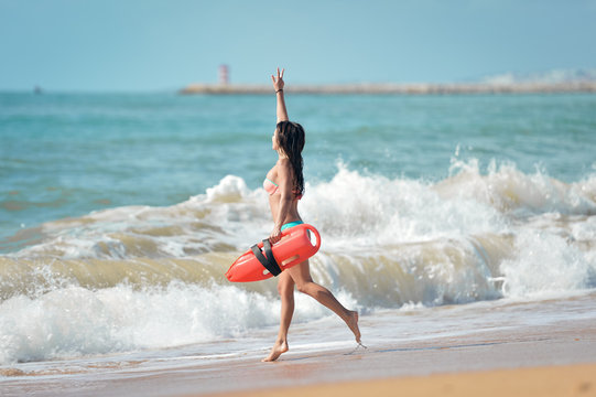 Fit lady in bikini with life-saver running into stormy ocean