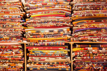 A large selction of blankets and their patterns on a shelf