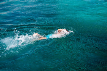 Single swimmer swimming in blue clear water