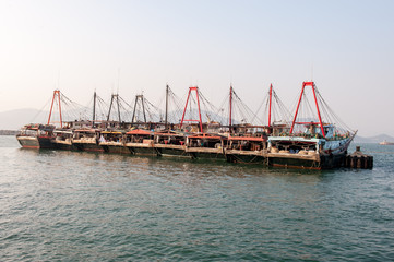Row of large Chinese fishing boats on water