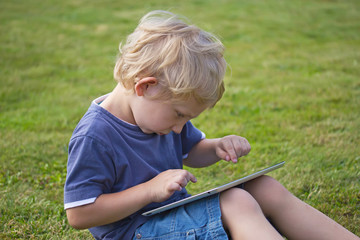 The blond boy is playing with the PC tablet outdoors