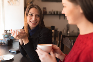 Two girlfriends talking over coffee in cafe