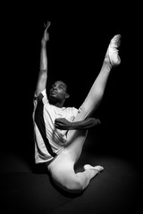 Classical ballet dancer warming up with stretches in black and white