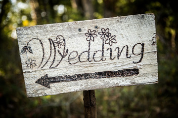 Rustic wedding arrow sign on a shovel.