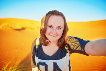 Happy tourist taking selfie with sand dunes in Sahara