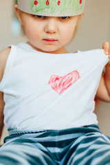 Little girl showing heart on your shirt