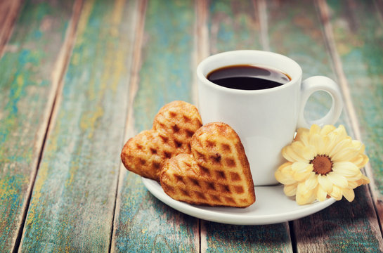 Waffle biscuits in shape of heart with cup of coffee and flower on rustic background for Valentines day, vintage toned