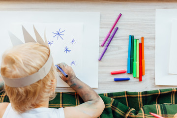 Little boy drawing snowflakes on paper. Children's Creative Work