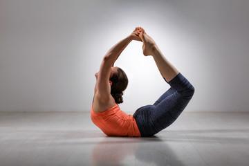 Sporty fit woman practices yoga asana Dhanurasana