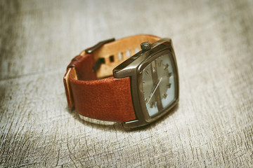 men's wrist watch with leather strap are on the table