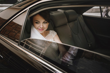 gorgeous elegant happy stylish brunette bride in luxury car on t