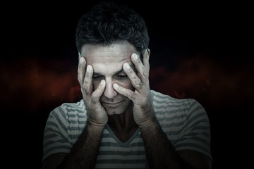 Composite image of upset man with head in hands