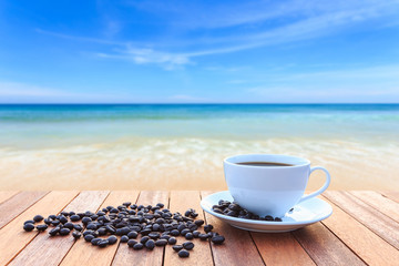 White coffee cup and coffee beans on wood table and view of suns