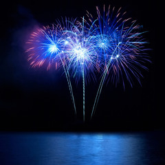 Blue fireworks above water