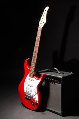 Electric guitar with amplifier on black background
