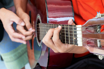 blurred man's hands playing acoustic guitar, and teaching guitar