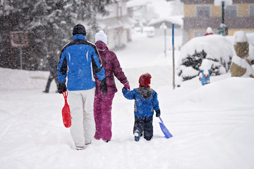 Happy family, going out wintertime to slide