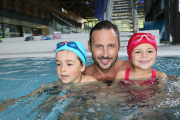 Man with kids in public swimming-pool