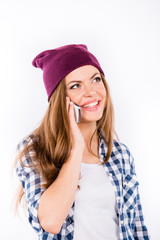 young beautiful girl in a hat hipster talking on the phone