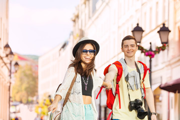 Girl with sunglasses holds hand of young man