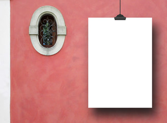 Single hanged empty paper sheet frame with clip on red plastered wall background with small oval historical window nearby