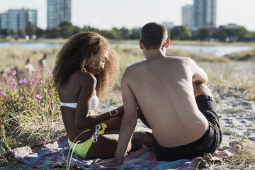 Mixed race couple on beach with urban landscape in the backgroun