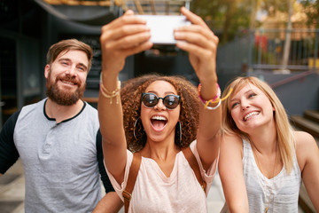 Group of smiling friends taking selfie with smart phone
