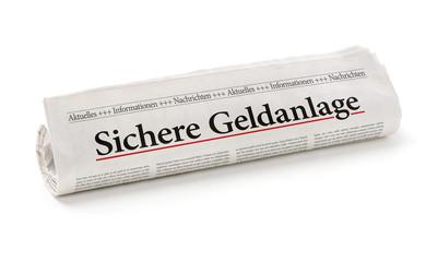 Zeitungsrolle mit der Überschrift Sichere Geldanlage