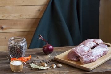 Raw pork fillet with spices and vegetables on the wood background