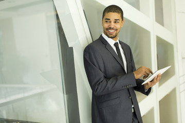 Young black man with tablet in the office