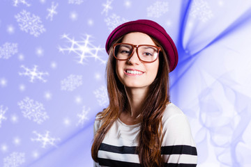 Young lady with sweet smile on blue graphic snowflakes background
