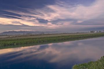 riflessi colorati sull'acqua del canale al tramonto