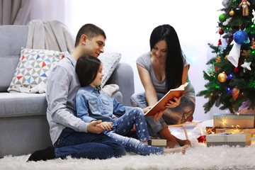 Happy family read book in the decorated Christmas room