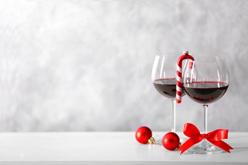 Two glasses of wine with christmas accessories on grey wall background