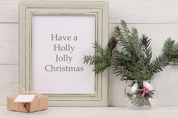 Have a Holly Jolly Christmas  poster in  shabby chick frame,  fir branch and vintage gift box with with copy space blank tag on white background. Scandinavian style home interior decoration