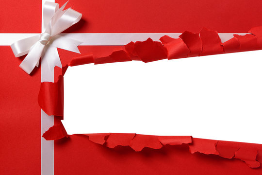 Christmas gift torn open strip, white ribbon bow, red wrapping paper