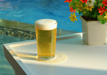 Beer mugs by swimming pool in tropical resort