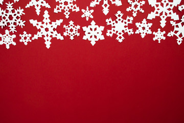 The paper snow flakes on the red background. Christmas red theme. Top view with copy space.
